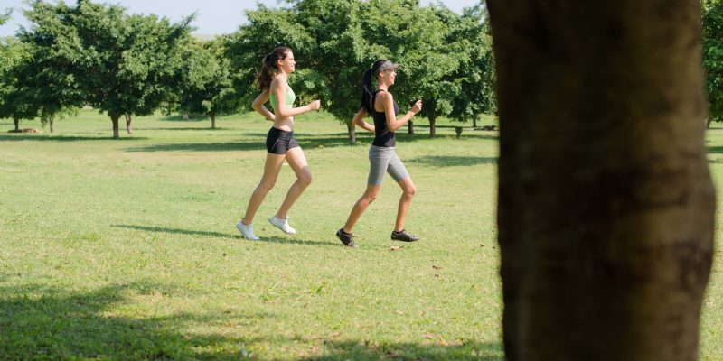 Sport with two young women jogging in city park